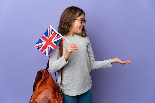 Kind, das eine flagge des vereinigten königreichs über isoliertem hintergrund mit überraschungsausdruck hält, während es zur seite schaut