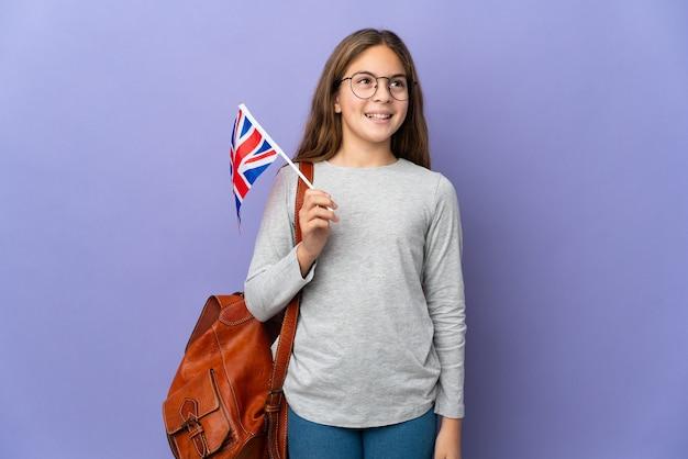 Kind, das eine flagge großbritanniens über isoliertem hintergrund hält, der eine idee beim nachschlagen denkt