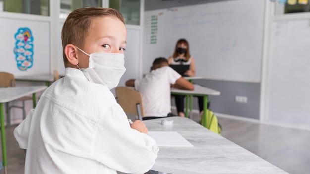 Kind, das eine gesichtsmaske im klassenzimmer trägt