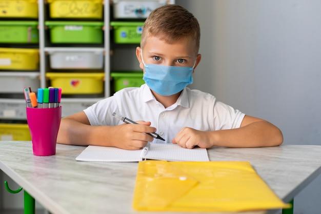 Kind, das eine gesichtsmaske in der pandemiezeit trägt