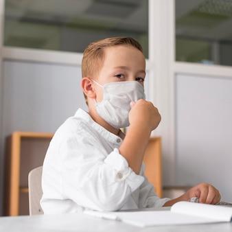 Kind, das eine medizinische maske im klassenzimmer trägt