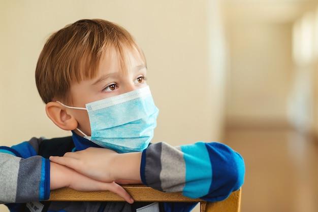 Kind, das eine schützende gesichtsmaske trägt. gesichtsmaske zur vorbeugung von virusinfektionen oder umweltverschmutzung. quarantänekonzept.