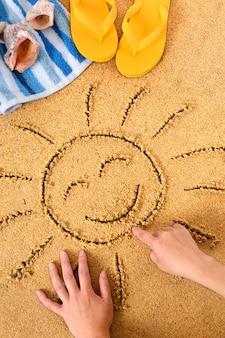 Kind, das eine sonne zeichnung im sand