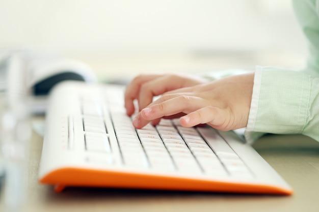 Kind, das eine tastatur eintippt