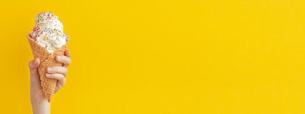 Kind, das eine vanille-eistüte auf einem hellen gelben und blauen süßen nachtisch verziert, verziert mit bunten streuseln, nahaufnahme