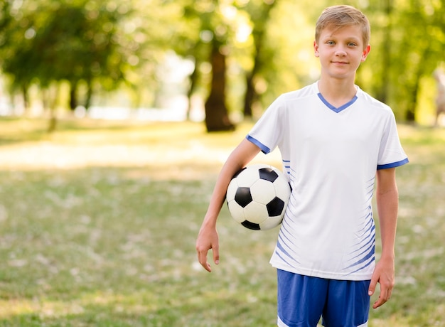 Kind, das einen fußball im freien hält
