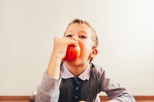 Kind, das einen geschmackvollen apfel, weißen hintergrund, konzept der gesunden nahrung lokalisiert beißt.