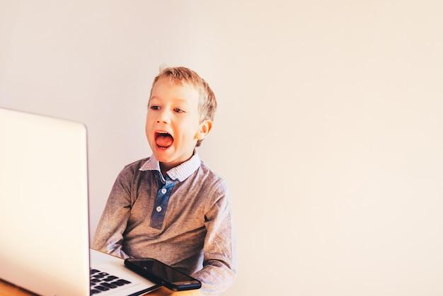 Kind, das einen laptop verwendet und mit gesten seinen erfolg im geschäft feiert, indem er viel geld verdient.