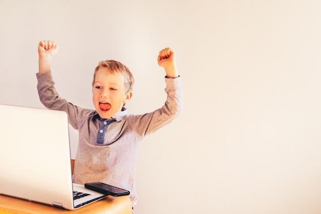 Kind, das einen laptop verwendet und über seinen erfolg im geschäft lacht.