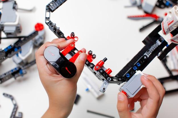 Kind, das einen roboter mit spielzeugblöcken und drähten macht