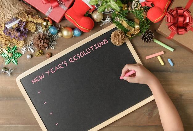 Kind, das entschließung des neuen jahres auf schwarzes brett schreibt