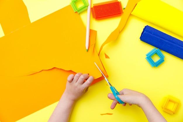 Kind, das farbiges orange papier mit einer schere auf einem tisch für etwas handwerk schneidet