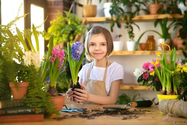 Kind, das frühlingsblumen pflanzt. gärtnerin des kleinen mädchens pflanzt hyazinthe. mädchen, das hyazinthe im blumentopf hält. kind, das sich um pflanzen kümmert. gartenwerkzeuge. speicherplatz kopieren.