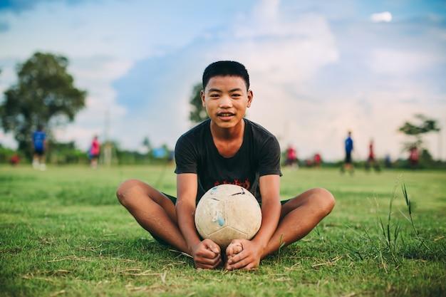 Kind, das fußballfußball für übung in der ländlichen gegend der gemeinschaft spielt
