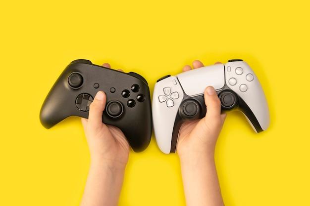 Kind, das gamecontroller in gelbem hintergrund hält