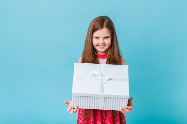 Kind, das geschenke auf einer blauen weihnachtszeit oder geburtstag hält