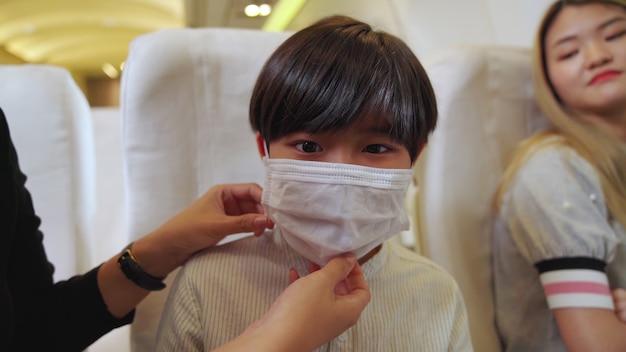 Kind, das gesichtsmaske in einem flugzeug trägt
