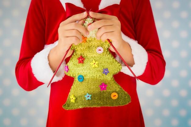 Kind, das gestrickten weihnachtsbaum hält. weihnachtsferienkonzept