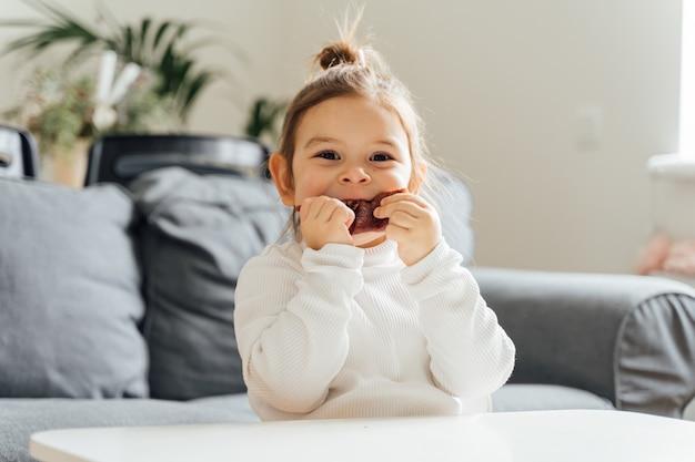 Kind, das getrocknetes fruchtleder für snack zu hause isst. natürliche süßigkeiten ohne zucker für kinder. vegetarische diät. natürlicher kleinkindsnack. hochwertiges foto
