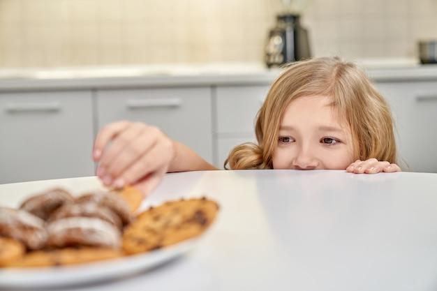 Kind, das heimlich amerikanische kekse vom teller nimmt.