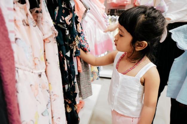 Kind, das ihre eigenen kleider vom kinderstoff-gestell im bekleidungsgeschäft auswählt.