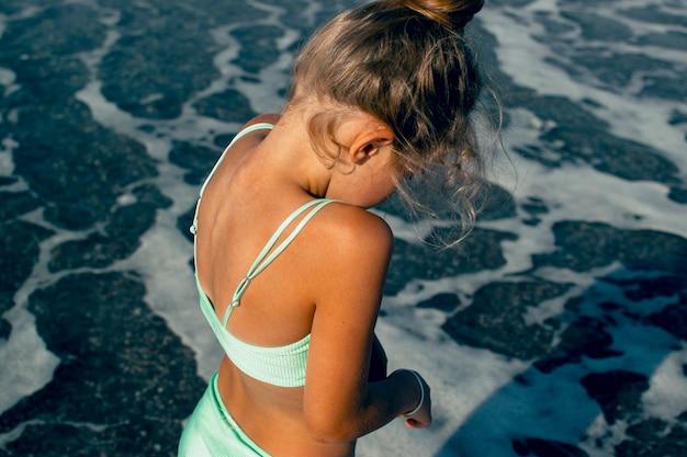 Kind, das im badeanzug am meer läuft und spielt