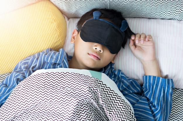 Kind, das im bett unter der decke zu hause schläft.