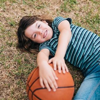 Kind, das im gras liegt und ball hält