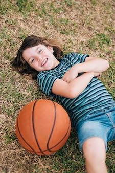 Kind, das im gras mit ball liegt