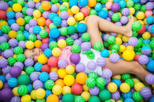 Kind, das im pool mit plastikkugeln liegt