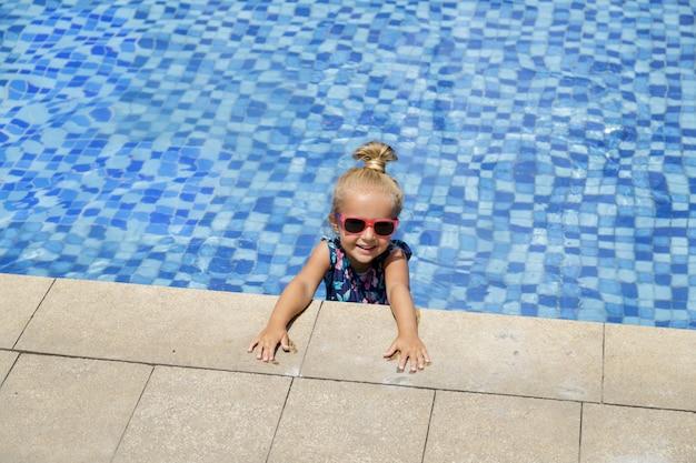 Kind, das im swimmingpool spielt. sommerurlaub mit kindern.