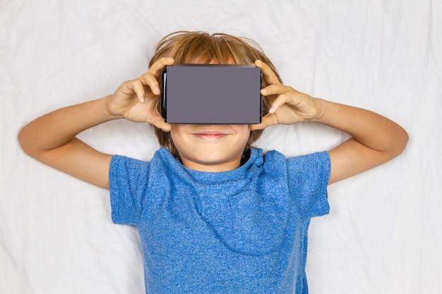Kind, das im weißen bett mit der virtuellen 3d-realität liegt