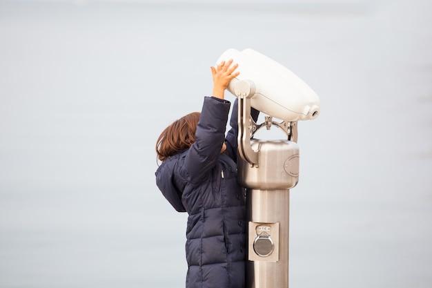 Kind, das in ein touristisches fernglas neben dem meer in triest schaut