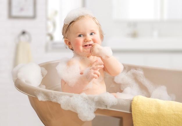 Kind, das in einem badezimmer im schaum sich wäscht.