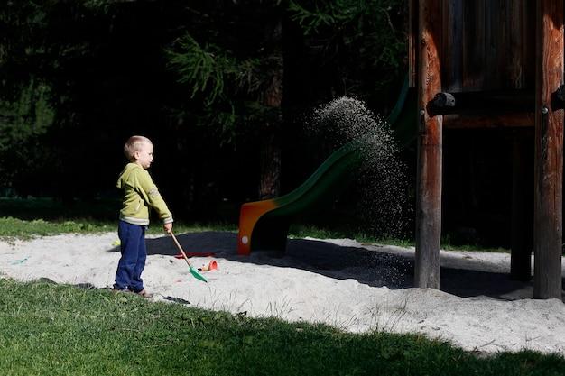 Kind, das in einem wasserkreislauf nahe den schweizer bergen spielt.