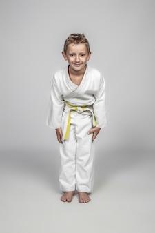 Kind, das kampfkunstjudogi in der rei position trägt