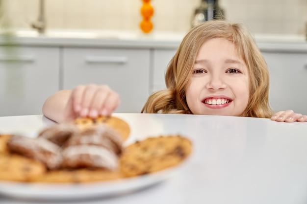 Kind, das kekse mit rosinen vom tisch versteckt und nimmt.