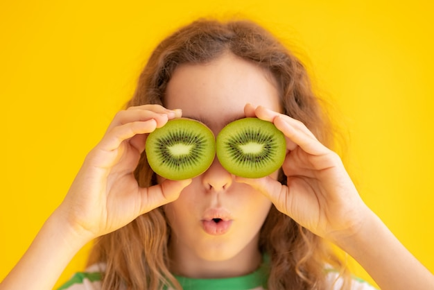 Kind, das kiwihälften anstelle der sonnenbrille hält