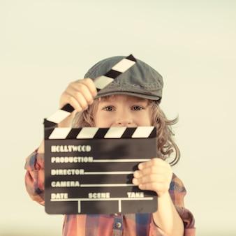 Kind, das klappenbrett in den händen hält. kinokonzept. retro-stil