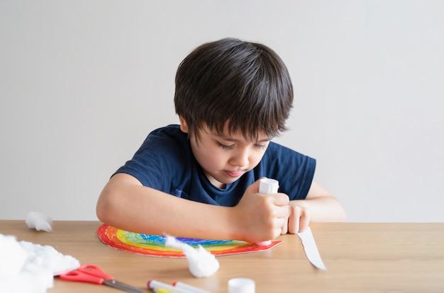 Kind, das klebestift auf papier für das aufkleben von watte als dekorative elemente für wolken auf regenbogen setzt