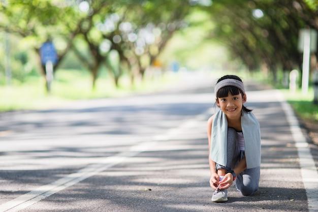 Kind, das laufschuhe bindet. glückliche lustige fitnessfrau des kleinen asiatischen mädchens, die am morgen läuft. athletisches junges kind, das in der natur läuft. gesunder lebensstil