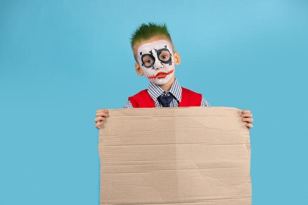 Kind, das leeren protestkarton lokalisiert auf blauer wand hält. soziale probleme und menschenkonzept.