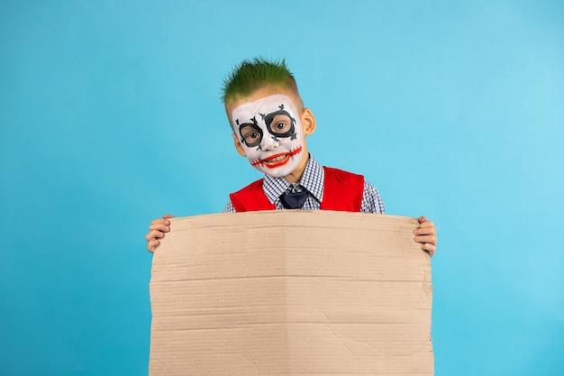 Kind, das leeren protestkarton mit freiem seitenraum lokalisiert auf blau hält. soziale probleme. halloween.