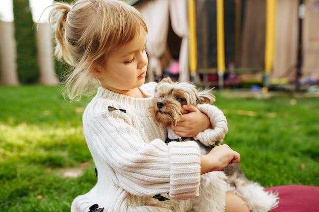 Kind, das lustigen hund im garten umarmt, beste freunde. kind mit welpen, der auf dem rasen auf hinterhof sitzt. glückliche kindheit