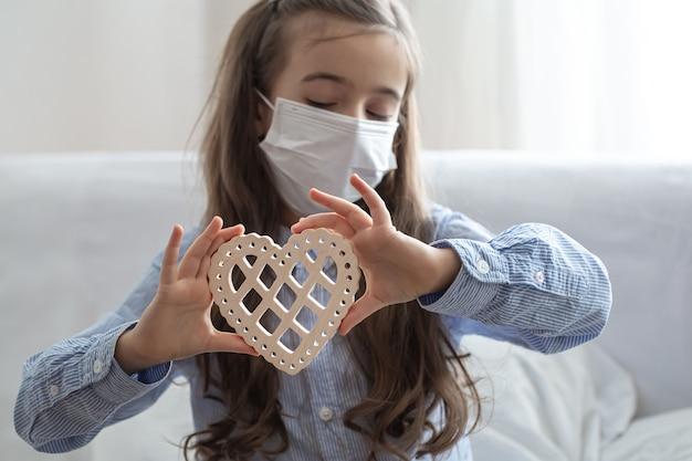 Kind, das medizinische schützende gesichtsmaske zum gesundheitsschutz von coronavirus trägt, hält hölzernes herz.