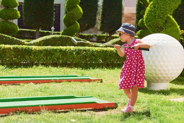 Kind, das minigolf auf kunstrasen spielt.