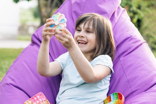 Kind, das mit antistress spielt, einfaches grübchen-zappel-spielzeug mit trendigem silikondruck-pop-it-spielzeug