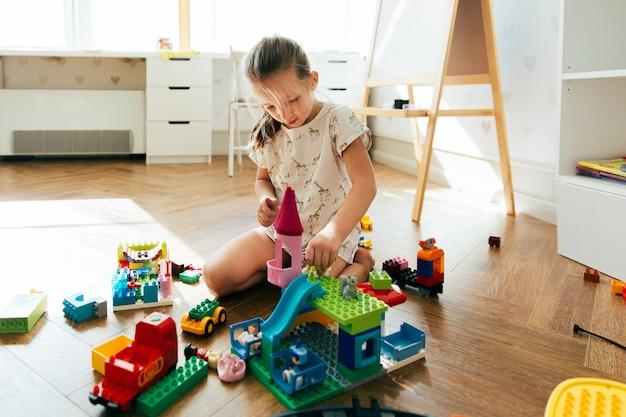 Kind, das mit bunten bauklötzen spielt. gebäudeturm des kleinen mädchens von blockspielwaren. pädagogisches und kreatives spielzeug und spiele für kleine kinder. freizeit und chaos zu hause