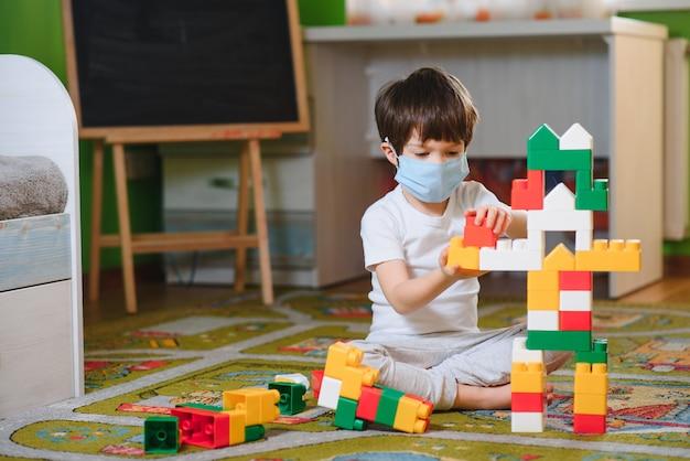 Kind, das mit bunten spielzeugblöcken spielt. kleiner junge, der turm zu hause oder in der kindertagesstätte baut. lernspielzeug für kleine kinder