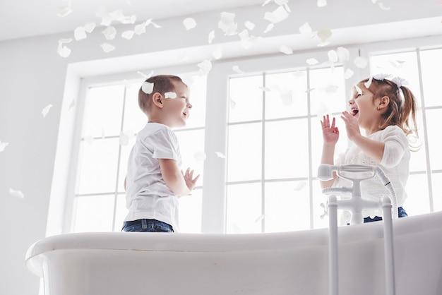 Kind, das mit den rosafarbenen blumenblättern im hauptbadezimmer spielt. kleines mädchen und junge, die zusammen spaß und freude fawing sind. kindheit und die verwirklichung von träumen, fantasie, phantasie